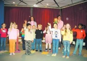 """""""Tschüss Maggie!"""": Die Kinder aus dem Englischkurs des Liebfrauen-Kindergartens verabschieden sich von der Handpuppe und den Schülerinnen der Elisabeth-von-Rantzau-Schule, die mit ihnen an acht Vormittagen Englisch geübt haben. Foto: Barth"""